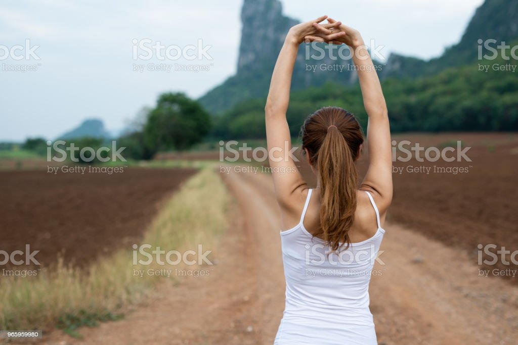 Back view of young asian fitness woman are stretching muscles before exercise. running and jogging on mountain road. The concept of health and fitness - Royalty-free Adulto Foto de stock