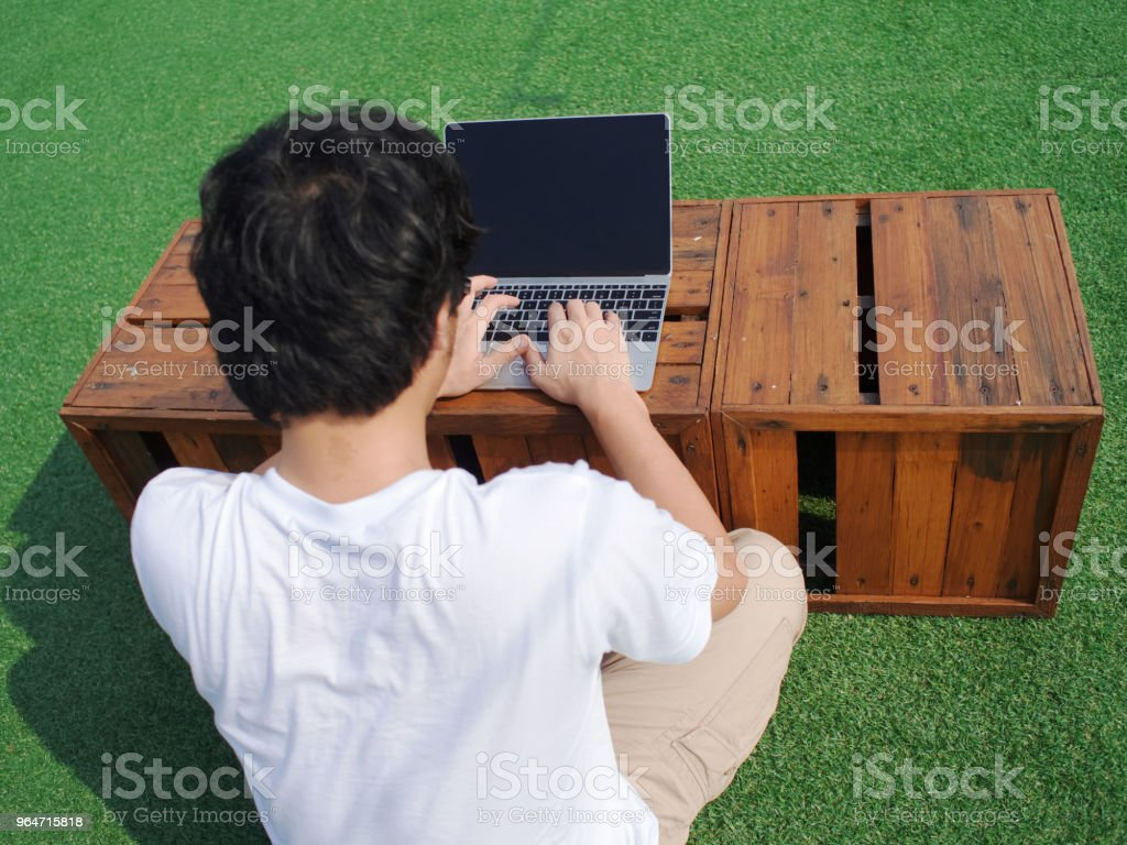 Back view of young Asian man using computer laptop at outdoors. royalty-free stock photo