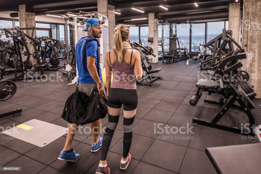 Back view of young athletic couple entering the gym and communicating. stock photo