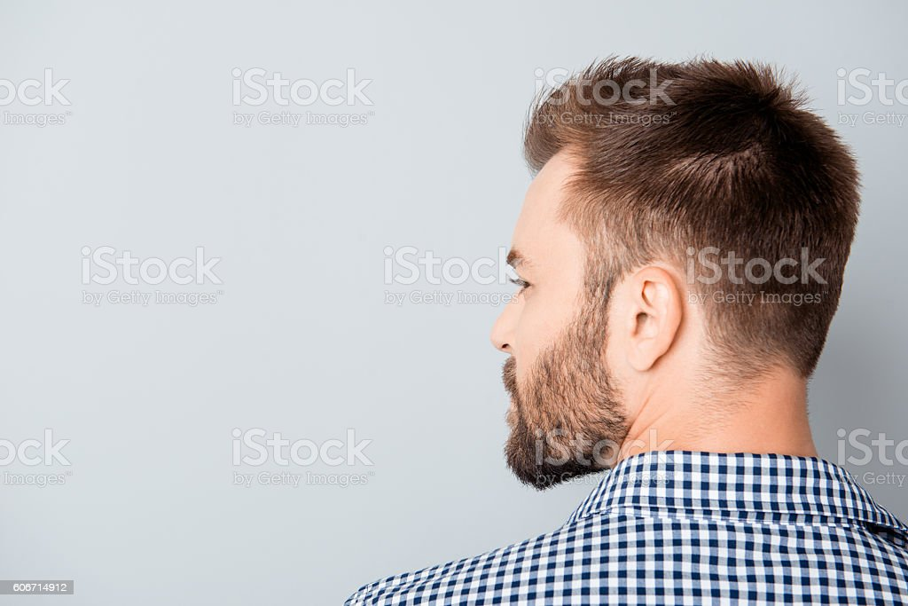 Back view of young bearded brunet man on gray background stock photo