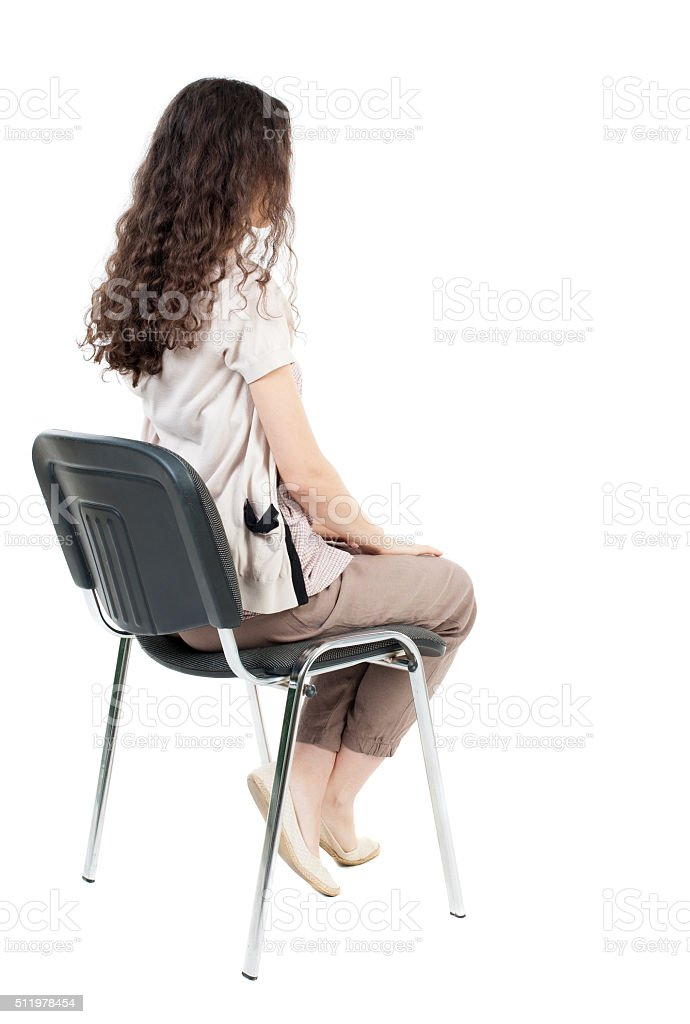 back view of young beautiful  woman sitting on chair. stock photo