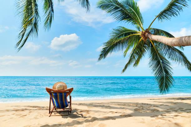 rückansicht der jungen schönen frau sonnen sich und entspannen sie am tropischen strand mit kopierraum - sun chair stock-fotos und bilder