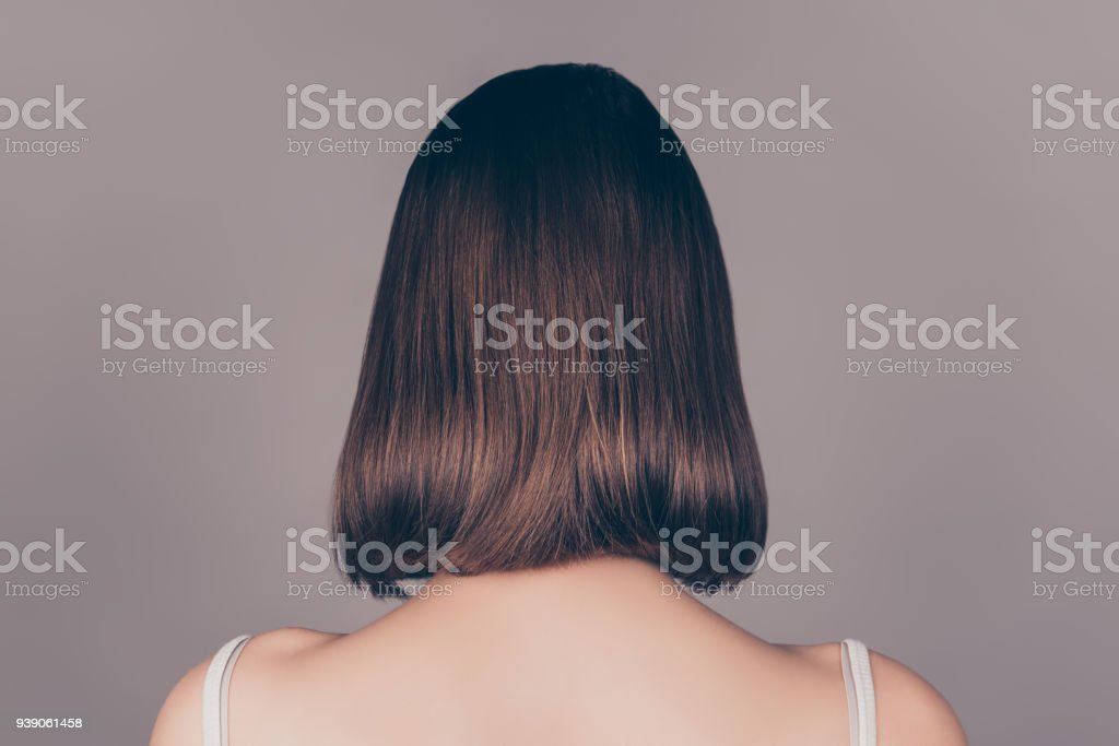 Back view of young beautiful wonam with short symmetric hair isolated on gray background stock photo