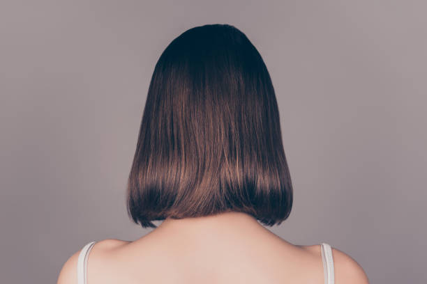 back view of young beautiful wonam with short symmetric hair isolated on gray background - capelli corti foto e immagini stock