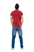 Back view of young casual man with hands in pockets looking up. Full body length portrait isolated over white studio background.