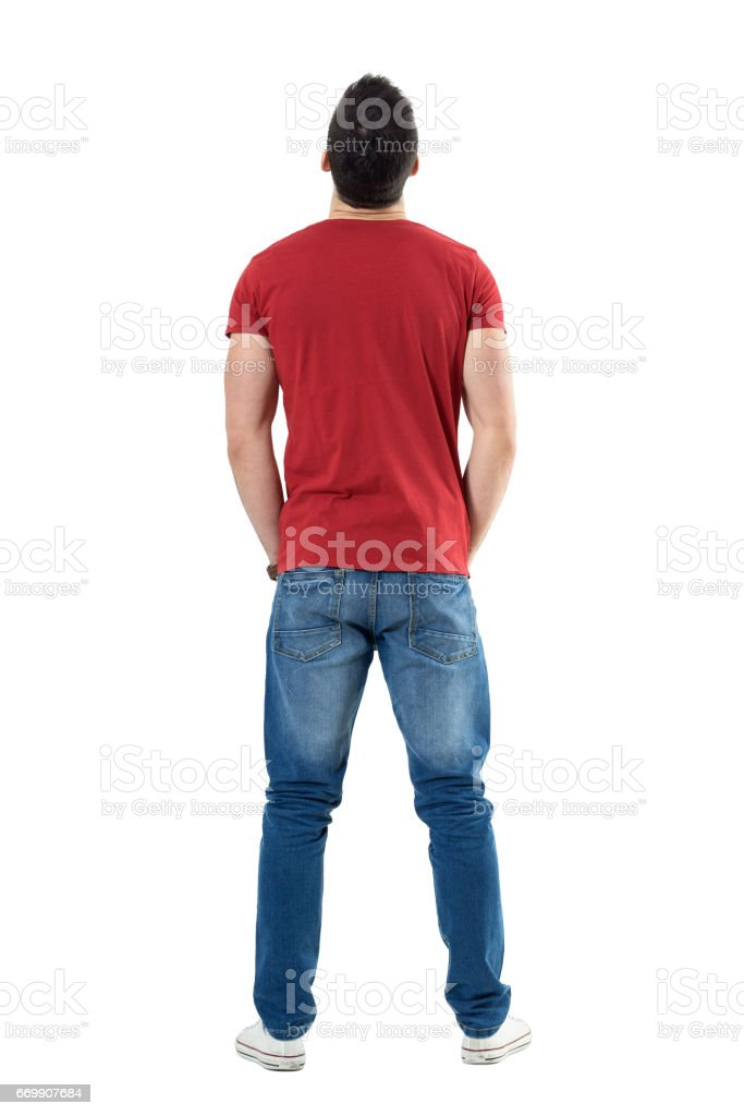 Back view of young casual man with hands in pockets looking up stock photo