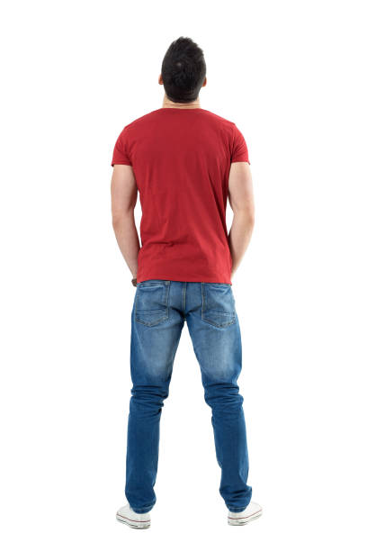 back view of young casual man with hands in pockets looking up - rear view stock photos and pictures
