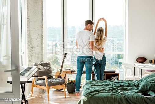 istock back view of young couple standing at window 1051293606