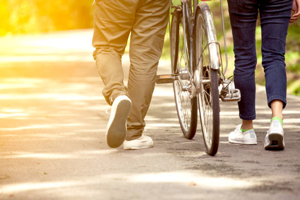 Back view of young couple walking  together with bicycle in the garden stock photo