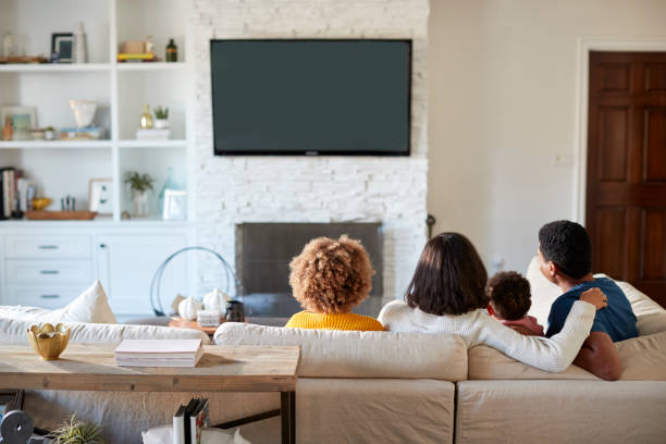 back view of young family sitting on the sofa and watching tv together in their living room - tv e familia e ecrã imagens e fotografias de stock