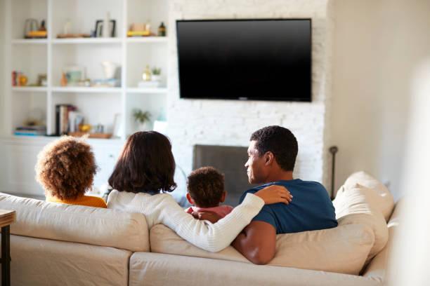 back view of young family sitting on the sofa and watching tv together in their living room, close up - tv e familia e ecrã imagens e fotografias de stock