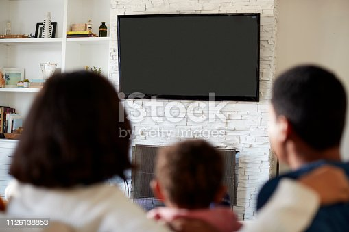 Back view of young family sitting on the sofa and watching TV together in their living room, close up, focus on television