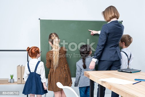istock back view of young female teacher with multiethnic students standing at blackboard 834598710
