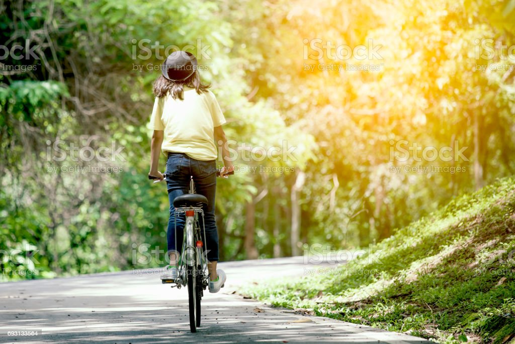 Back view of young girl riding bicycle in the garden stock photo