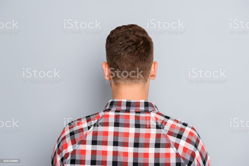 Back view of young guy in chekered shirt on gray background stock photo