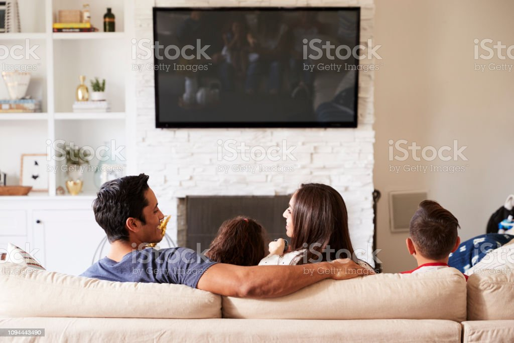 Back view of young Hispanic family of four sitting on the sofa watching TV, mum looking at dad stock photo