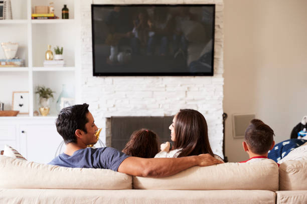 back view of young hispanic family of four sitting on the sofa watching tv, mum looking at dad - televisor imagens e fotografias de stock