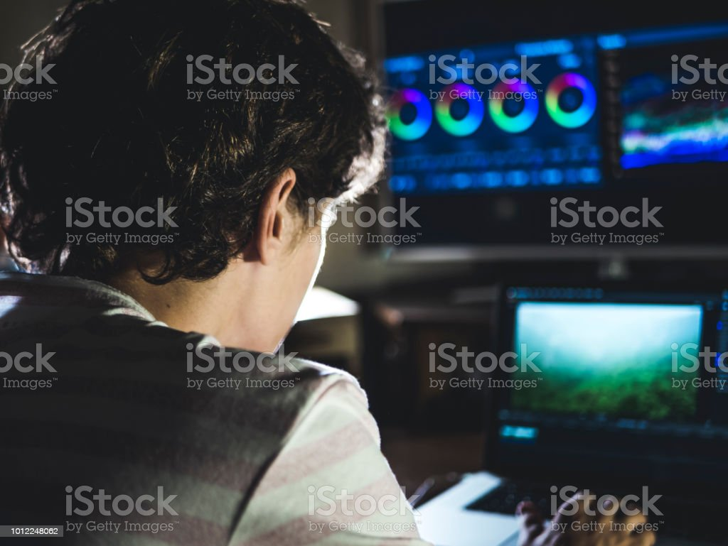 Vista posterior de la joven en el color oscuro estudio vídeo con ordenador portátil y el monitor externo de clasificación - foto de stock