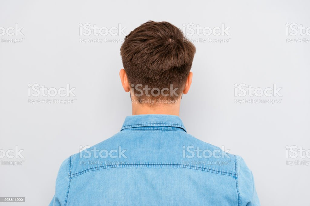 Back view of young man isolated on gray background stock photo