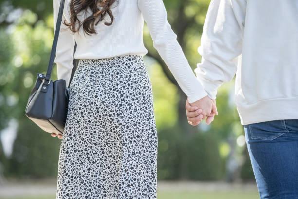 手をつなぐ若い男女の裏図 - ガールフレンド ストックフォトと画像