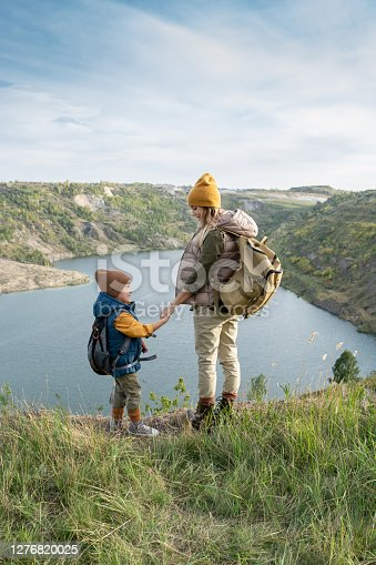 Back view of young mother and little son with backpacks holding by hands and looking at each other while standing in front of lake
