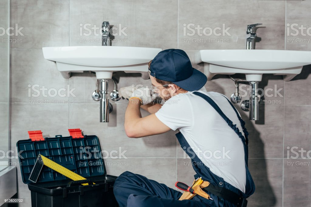 back view of young professional plumber fixing sink in bathroom stock photo