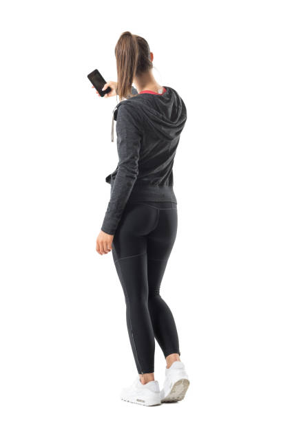 Back view of young sporty fit woman taking photo with smartphone. stock photo
