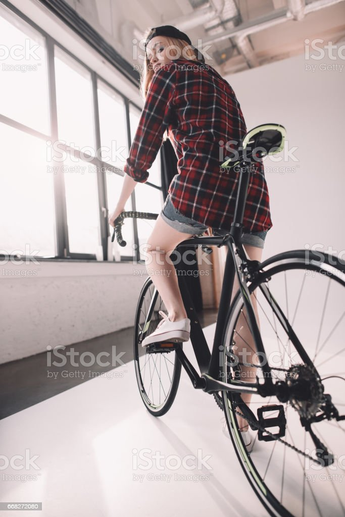 back view of young stylish woman riding bicycle foto stock royalty-free