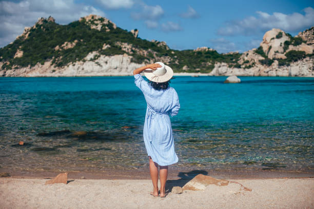 back view of young woman in hat relax in amazing sardinia beach - sardegna foto e immagini stock