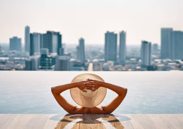 Rückansicht der jungen Frau im Hut entspannen im Pool auf dem Dach des Hotels und genießen Sie das Stadtbild – Foto