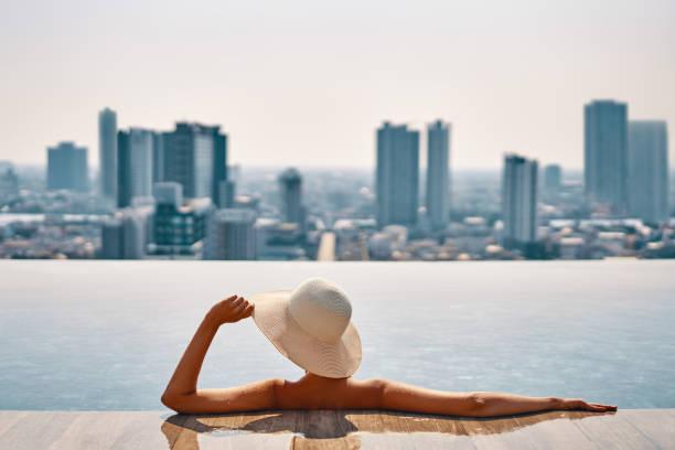 Vista trasera de la joven con sombrero relajarse en la piscina en la azotea del hotel y disfrutar del paisaje urbano - foto de stock
