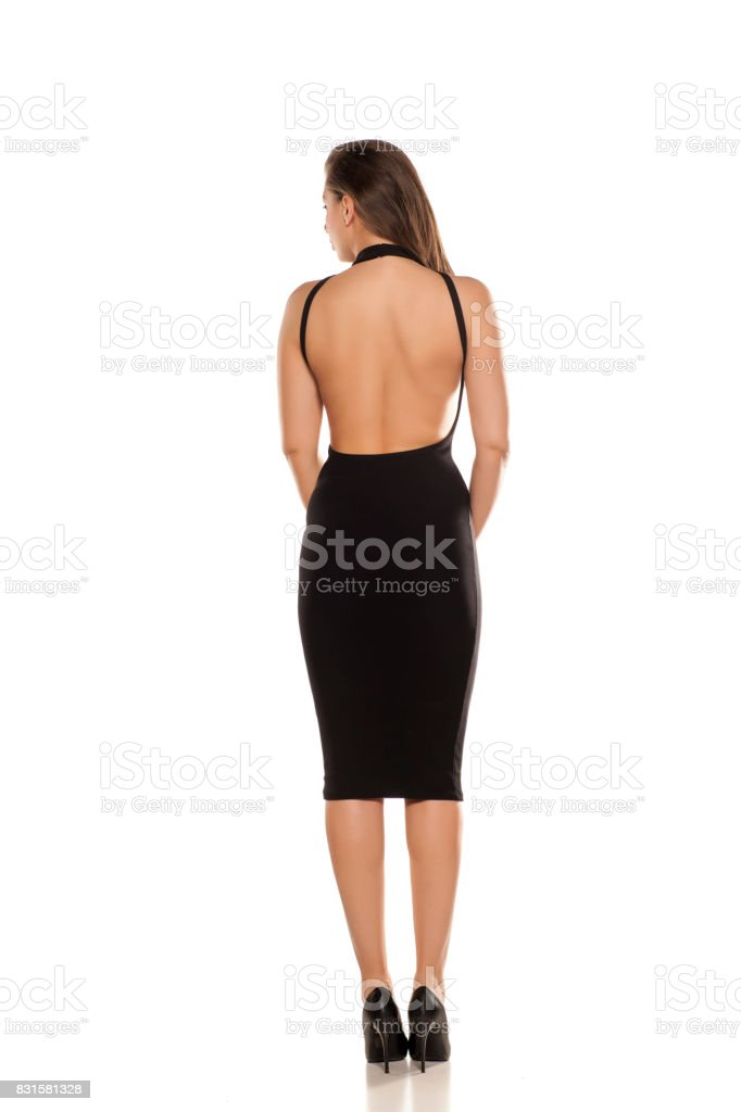 7f73705fa24 Back view of young woman in tight black dress on white background - Stock  image .
