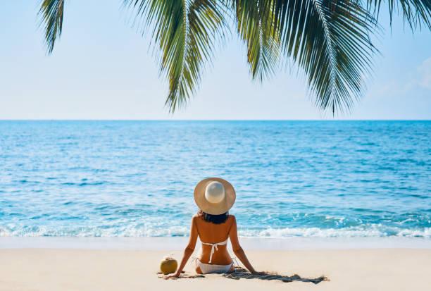 Rückansicht der jungen Frau entspannen allein am tropischen Strand – Foto