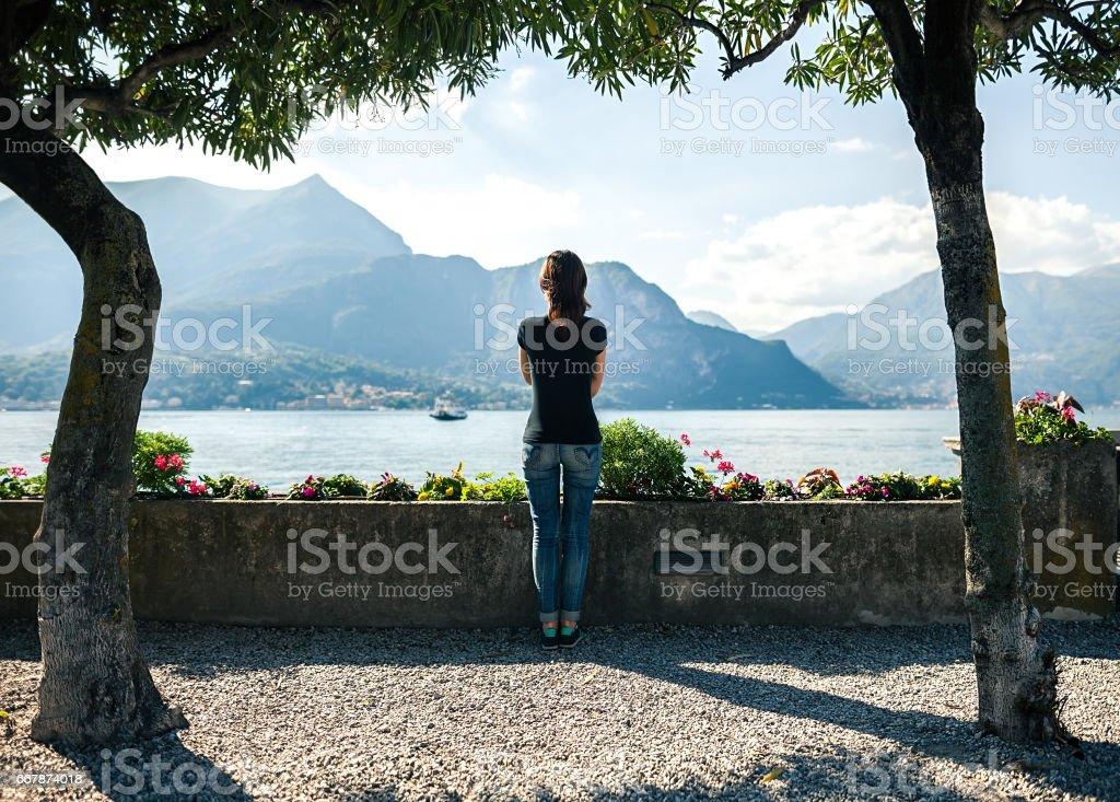 Vista de jovem relaxante traseira no cais do Lago de montanha Como em Itália - foto de acervo