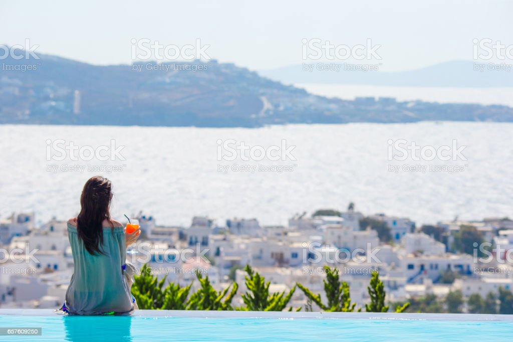 Back view of young woman relaxing on the edge of pool with amazing view on Greece stock photo