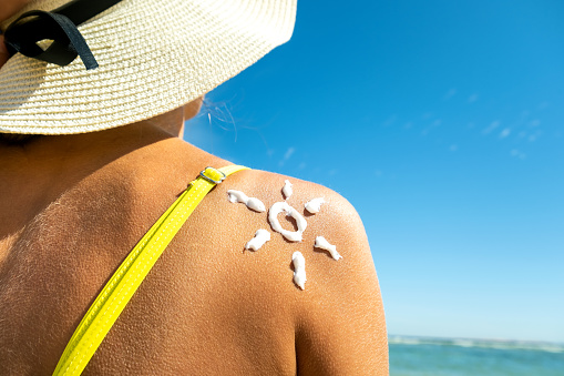 514258424 istock photo Back view of young woman tanning at the beach with sunscreen cream in sun shape on her shoulder. UV sunburn protection and sunblock skincare concept 1216791814