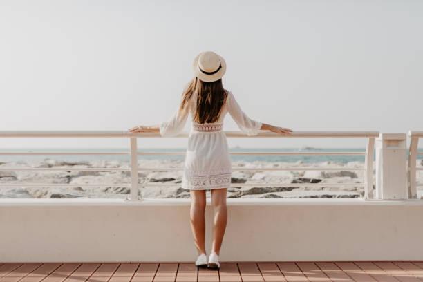 rückansicht des jungen frau zu fuß auf die promenade am meer suchen. ziel der vereinigten arabischen emirate. sommer urlaubsreisen. - hochzeitsreise dubai stock-fotos und bilder