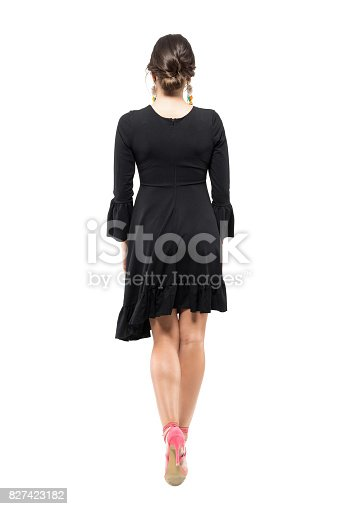 Back view of young woman with bun hairstyle and black flounced dress walking away. Full body length portrait isolated on white studio background.