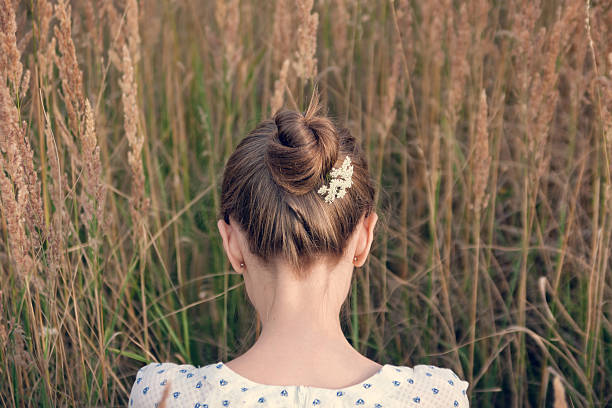 Back view of young woman with hair bun Back view of young woman with hair bun. human neck stock pictures, royalty-free photos & images