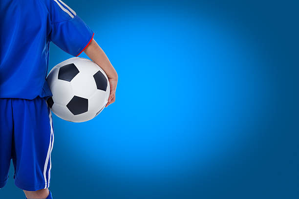 Back view of youth soccer player in blue uniform stock photo
