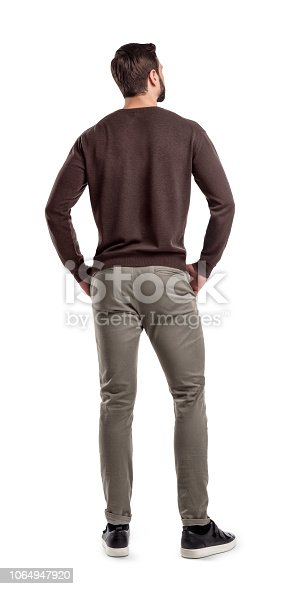 A back view on a modern fit and casually clothed man that stands in a relaxed posture and looks sideways. Man from back. Modern garb. Unrecognizable person.