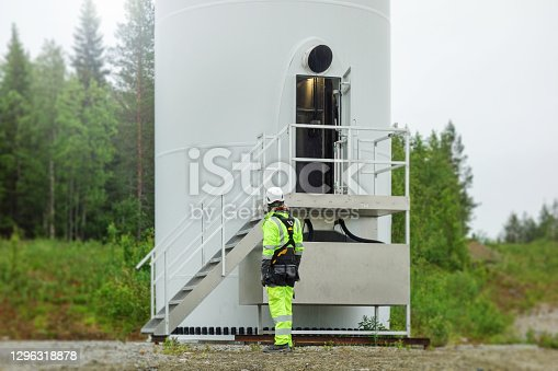 Back view on professional rope access technician standing front of onshore wind-turbine tower in Swede and looking on door.