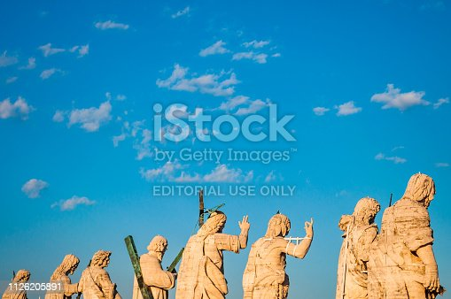 Vatican, Rome, Italy - November 16, 2018: Back view on the statues on the balustrade of St. Peter's Basilica facade represent Christ the Redeemer, St. John the Baptist and 11 Apostles