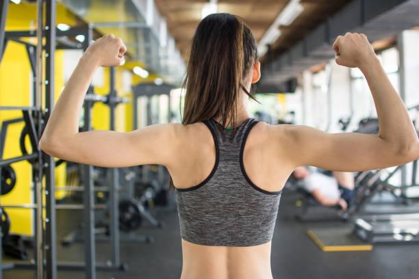 Rückblick auf die Rückenmuskulatur der jungen Fitness-Frau und ihre Bizeps im Fitnessstudio – Foto