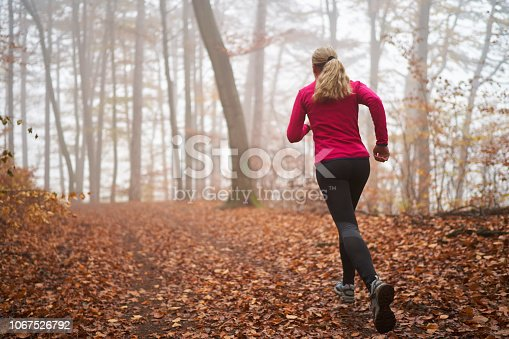 rear view 45 year old woman running in autumn forest foggy bad weather conditions cold october or november look