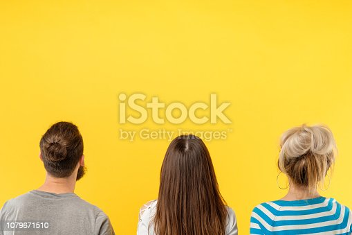 Back view of modern casual women and man standing in row against bright yellow background