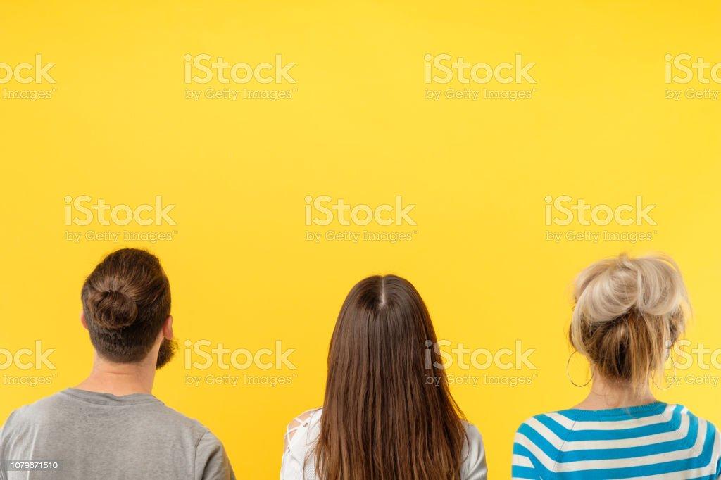 Personas en vista trasera pie fondo amarillo - foto de stock