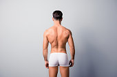 istock Back view photo of handsome confident guy with strong back and shoulders, wearing white underpants, isolated on grey background, copyspace 926172560