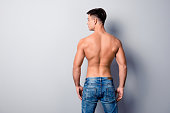 Back view photo of healthy strong handsome perfect man' body, he is wearing jeans, isolated on grey background, copyspace