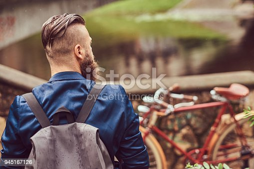 istock Back view portrait of a bearded male with a haircut dressed in casual clothes with a backpack, sitting in a city park 945167126
